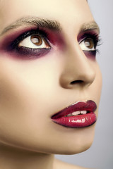 Beautiful face with pink eyes and lips on a gray background