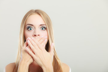 Amazed woman covering her mouth with hands