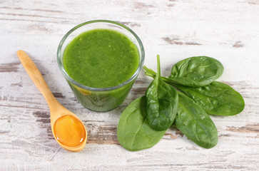 Cocktail from spinach with honey on old rustic wooden background, healthy nutrition