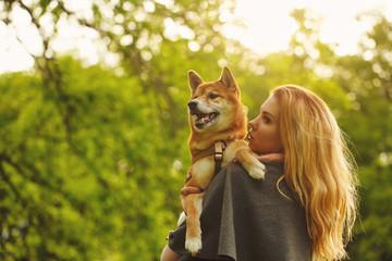 Girl and dog Shiba Inu embrace.