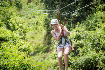 Beautiful woman riding a zip line in a lush tropical forest