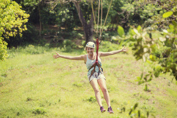 Happy woman riding a zip line in a lush tropical forest. Having fun with arms outstretched
