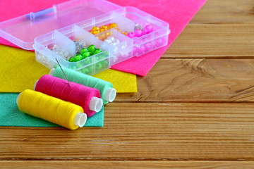 Organizer with various beads, colored thread, needle, felt pieces. Wooden background with empty space for text. Sewing kit
