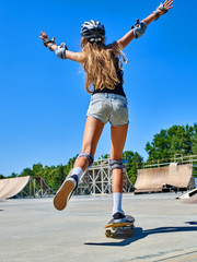 Teen skateboarding his skateboard on one leg outdoor. View from the back.