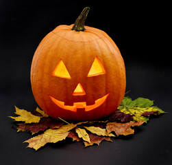 Halloween pumpkin with scary face and black background. Pumpkin, isolated on black background with autumn leaves.