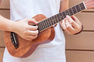 Teen asian women with ukulele in her free time.