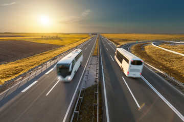 Fast travel buses on the highway at idyllic sunset