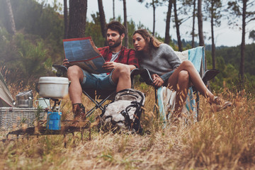 Young couple sitting together at their campsite looking at a map