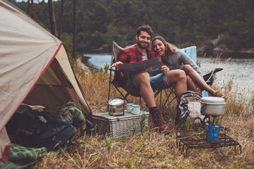 Loving couple camping by the lake using travel map