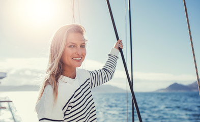 Beautiful young woman standing on the boat