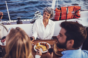 Senior woman with a young couple having meal on the boat