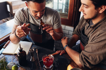 Two bartenders experimenting with creating cocktails