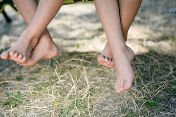 Outdoor picture of two children legs barefoot. Closeup of happy kids sitting on sunny countryside.