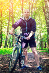 Cyclist with backpack, stand and holding bike, travels in the beautiful summer forest