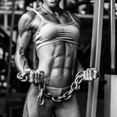 Strong athletic female body. Muscular woman with heavy chain