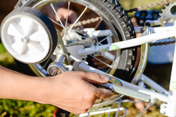 Closeup on hands of father fixing mechanism of the bicycle, green background outside