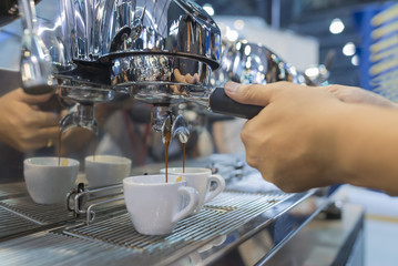 espresso pouring from coffee machine by professional coffee brewing.
