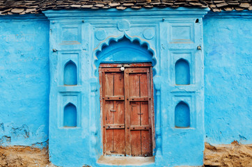 Blue painted traditional house with closed wooden door in India