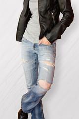 Fitter weiblicher Körper in blauer zerissener Jeans vor weißem Hintergrund