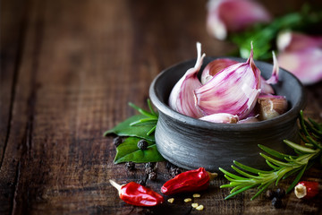 Cloves of purple garlic in a black bowl with rosemary, bay leaf, black pepper and chili pepper on dark rustic wooden background. With plenty of copy space for your text