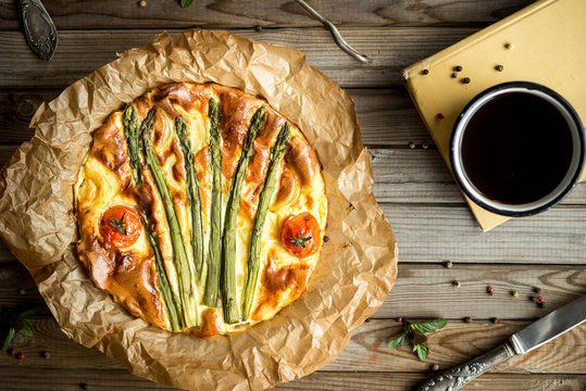 Pie with asparagus and tomatoes on wooden rustic table. Top view.