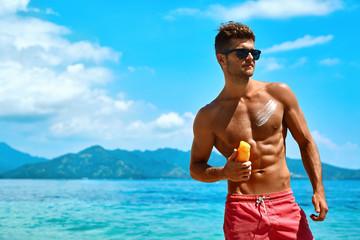 Sexy Man Tanning Using Sunscreen Cream On Body Skin. Summer