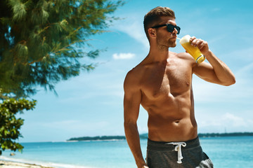Healthy Drink. Handsome Fitness Male Model Having Fun, Enjoying Travel Vacation. Portrait Of Athletic Sexy Man With Muscular Body Drinking Refreshing Juice Cocktail On Tropical Sea Beach. Summertime