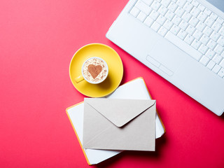 cup, envelope, notebook and laptop