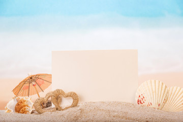 Blank  card with sea shells, hearts in  sand on  beach.