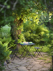 An outdoor table in a   flowering garden, Sweden.