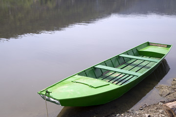 Old Green Wooden Boat Floating On Calm Lake, Water Reflection