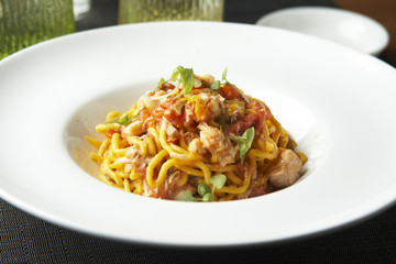 Fresh spaghetti with white fish ragout, capers and orange zest