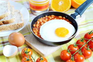 Fried egg with beans, toast bread, fresh juice, tomatoes and oranges