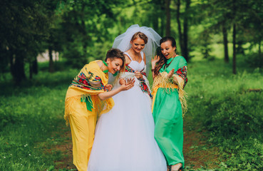 Bride shows ring their bridesmaid. Bridesmaid in shock and laughter surprise, joke. Bridesmaid in yellow and green dress. Bride have blonde hair.