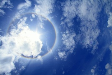 Sun corona on blue sky with clouds