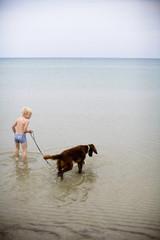 A boy and a dog bathing in the sea, Gotland, Sweden.