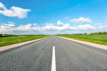 Asphalt road in green fields on blue cloudy sky background