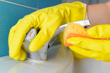 Cleaning - cleaning bathroom faucet with detergent in yellow rubber gloves