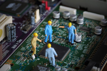 Selective focus of miniature engineer meeting, worker fixed problem and repair chip mainboard computer and use for business background.