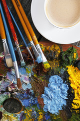 Set of artist brushes, a palette, and a cup of coffee on a wooden background