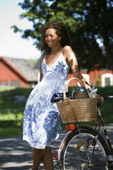 A smiling woman with a bicycle, Sweden.