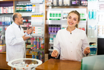 Pharmacist and assistant working at farmacy reception