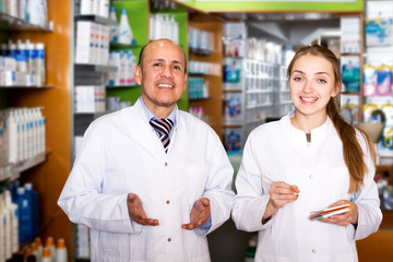 Pharmacist and pharmacy technician posing in modern farmacy
