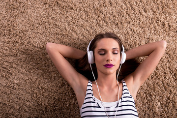 Charming young woman with headphones lying on the carpet and listening music.