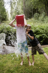 Boys playing with water in a garden a summer day, Sweden.
