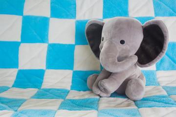 Cute Baby Elephant Stuffed Animal on a Blue Checkered Blanket