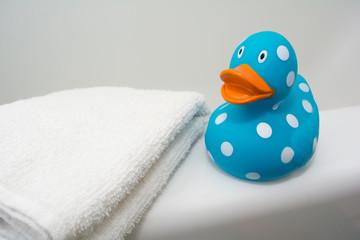Cute Rubber Duck beside a White Towel in a Bathroom
