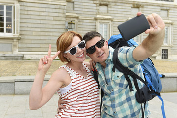 young American couple enjoying Spain holiday trip taking selfie photo self portrait with mobile phone