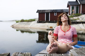 A woman sitting on a jetty in the archipelago of Stockholm, Sweden.