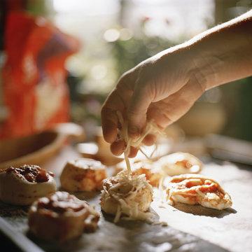 Man's hand garnishing mini pizza with cheese